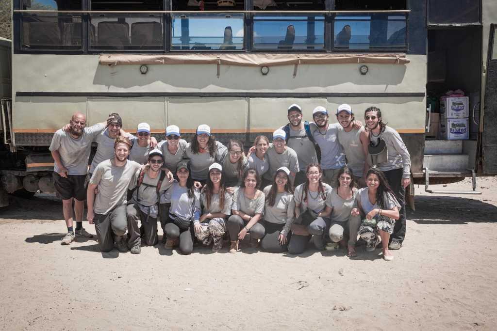 26 voluntarios de Sudáfrica, Estados Unidos y México frente al Jeep en el campamento de ayuda.