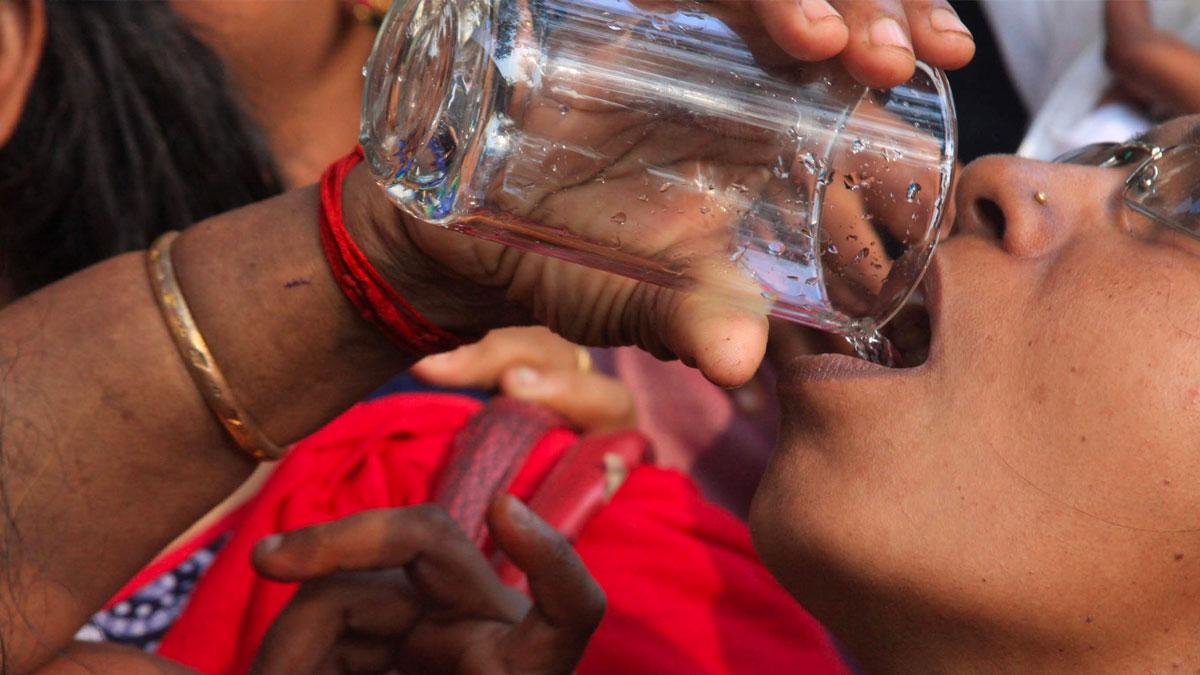 Una mujer toma agua potable gracias a un filtro de agua de CADENA.