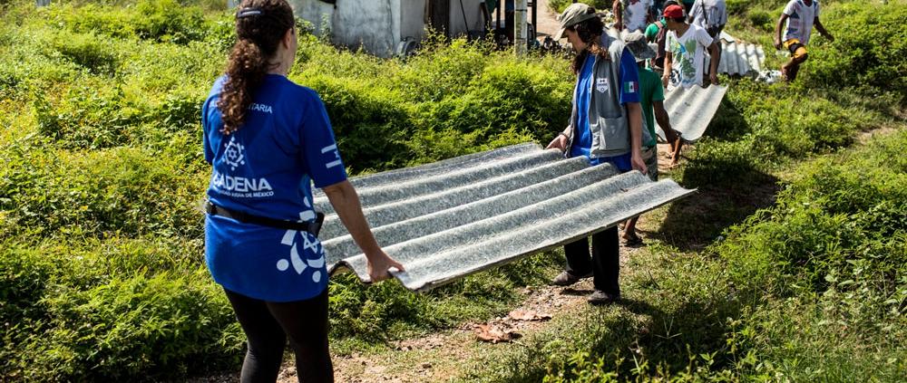 Voluntarias CADENA cargando un techo de lámina.