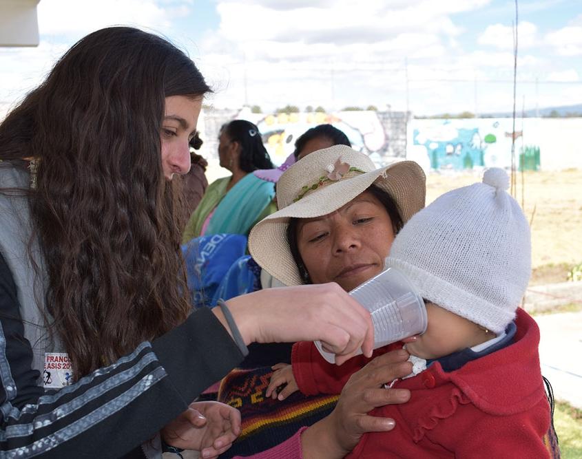 Mujer adolescente dando agua a un bebé.