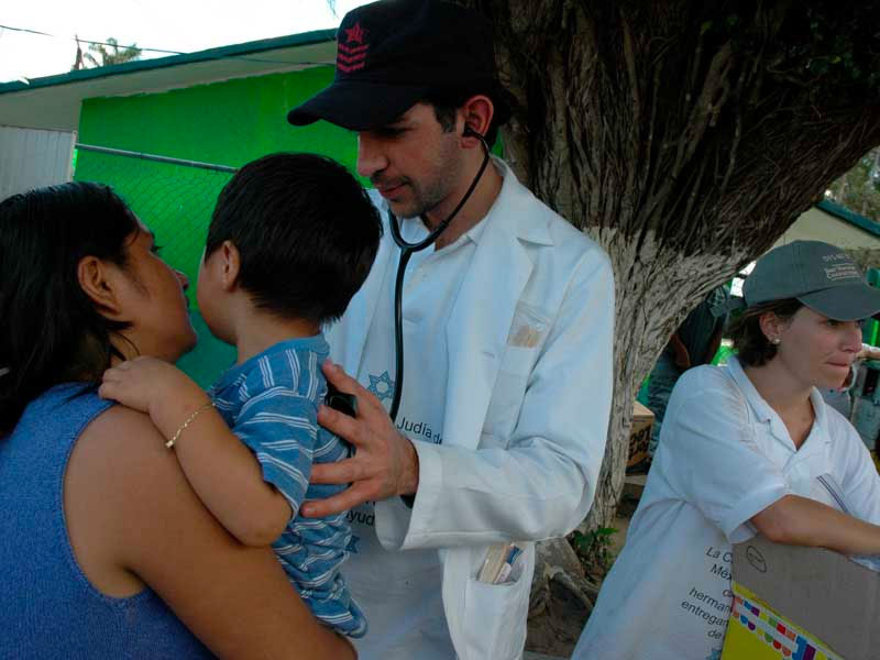 Un doctor voluntario de CADENA revisa a un niño en Tabasco