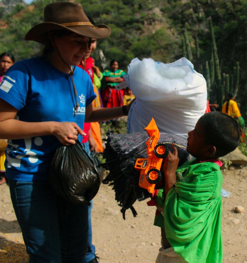 Un voluntario de CADENA entrega juguetes a un niño de la Sierra Tarahumara.